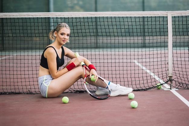 Tennisspielerin, die auf dem boden auf bruch sitzt