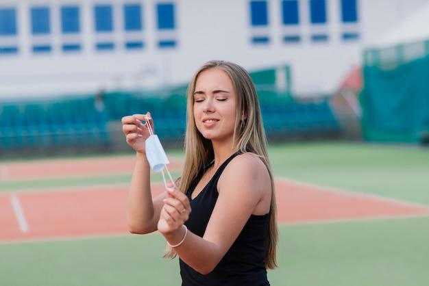 Tennisspielerin, die mit schutzmaske auf platz spielt
