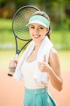 Tennisspielerin mit handtuch auf den schultern.