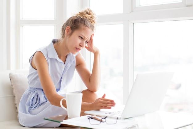 Tensed woman working und touching head auf loggia
