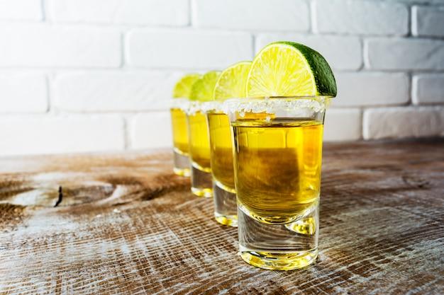 Tequila-aufnahmen auf dem rustikalen holztisch und der bemalten backsteinmauer.