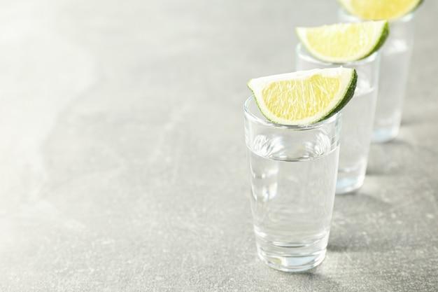 Tequila-aufnahmen mit limettenscheiben auf grau