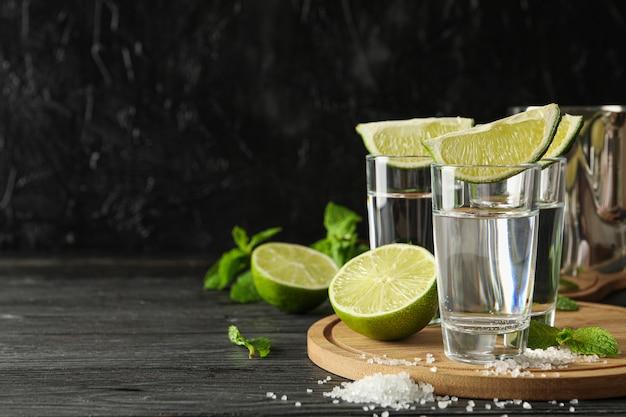 Tequila-aufnahmen mit limettenscheiben, salz und minze auf holz