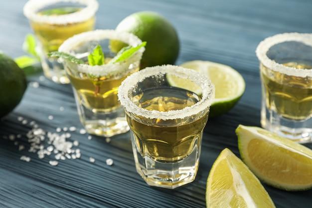 Tequila-aufnahmen mit salz, limettenscheiben und minze auf blauem holz
