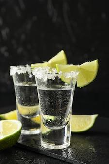Tequila-aufnahmen mit salz- und limettenscheiben auf schwarz nass