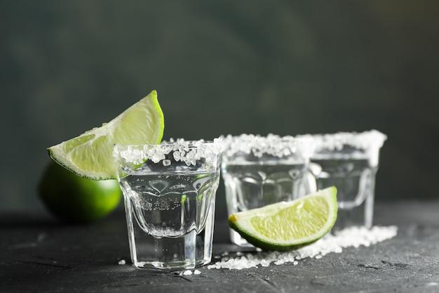 Tequila-aufnahmen mit salz- und limettenscheiben auf schwarz