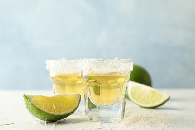 Tequila-aufnahmen mit salz- und limettenscheiben auf weiß