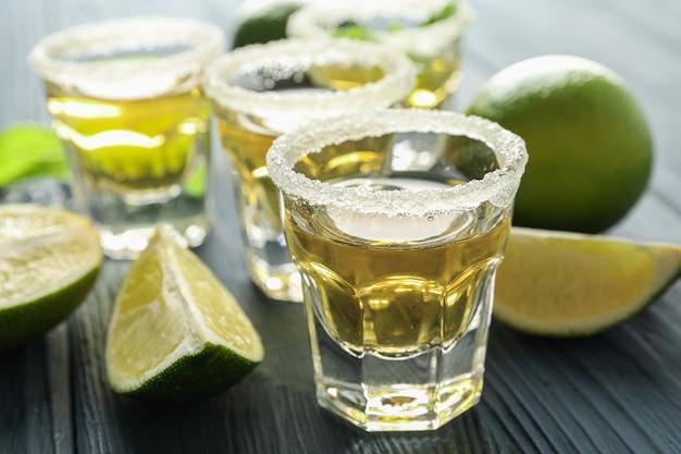 Tequila-aufnahmen, salz, limettenscheiben und minze auf holztisch, nahaufnahme