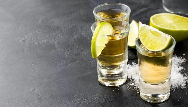 Tequila-aufnahmen und limettenscheiben mit kopierraum