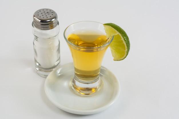 Tequila mit kalk auf dem weißen hintergrund