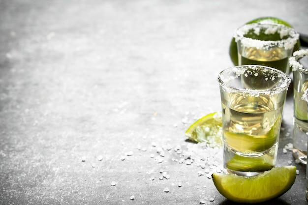 Tequila mit limette und salz. auf dem steintisch.