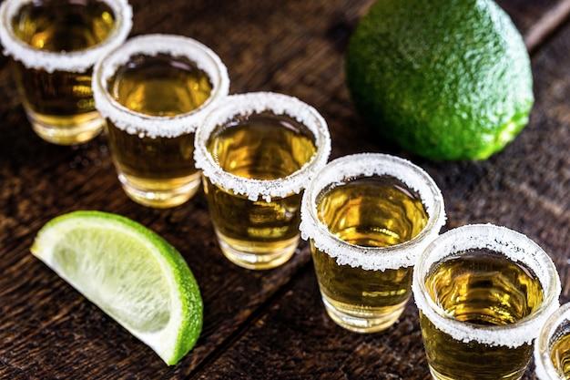Tequila mit zitrone und salz auf holz