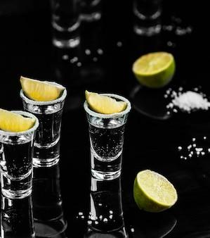 Tequila schießt mit zitrone auf den tisch