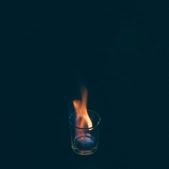 Tequila-schnapsglas auf feuer auf schwarzem hintergrund