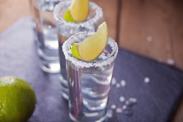 Tequila schoss mit kalk und seesalz auf schwarzem behälter, selektiver fokus