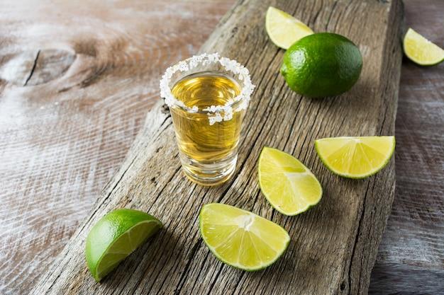 Tequila schoss mit kalkscheiben auf rustikalem hölzernem