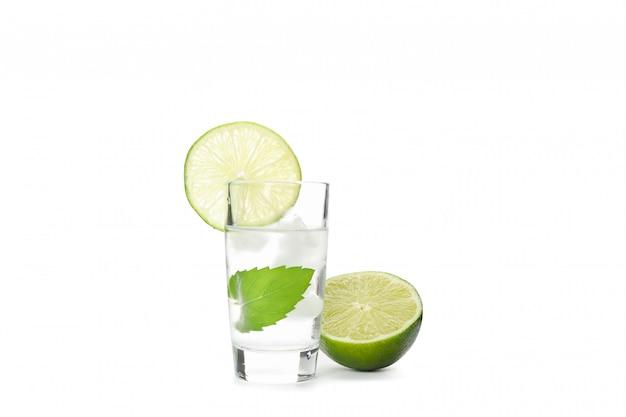 Tequila schoss mit limette, minze und eis isoliert auf weiß