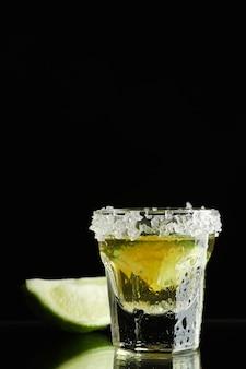 Tequila schoss mit limette und meersalz auf schwarz