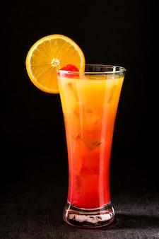 Tequila-sonnenaufgangcocktail im glas auf schwarzem