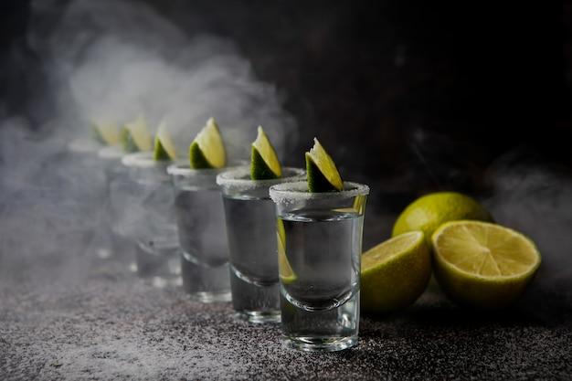 Tequila von der seite in einem glas, serviert mit limetten und salz