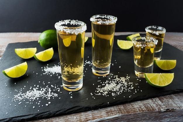 Tequilaschüsse mit kalk auf schwarzem steinhintergrund