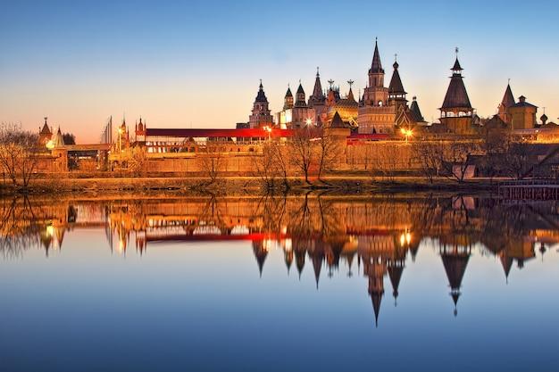 Teremki vom izmailovsky kreml in moskau mit spiegelung im wasser des teiches im licht der abendlichter