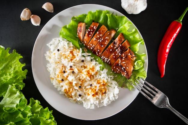 Teriyaki-huhn mit sesam, salat und reis auf einem weißen teller. gericht mit einer gabel auf einem schwarzen