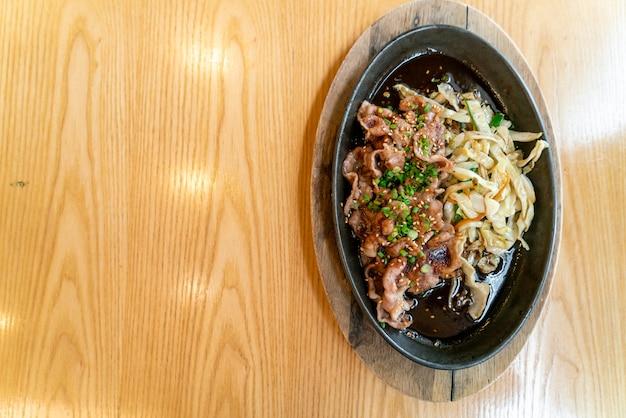 Teriyaki-schweinefleisch in heißer pfanne mit kohl. japanischer essensstil