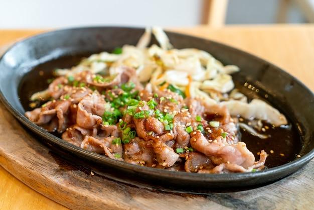 Teriyaki-schweinefleisch in heißer pfanne mit kohl