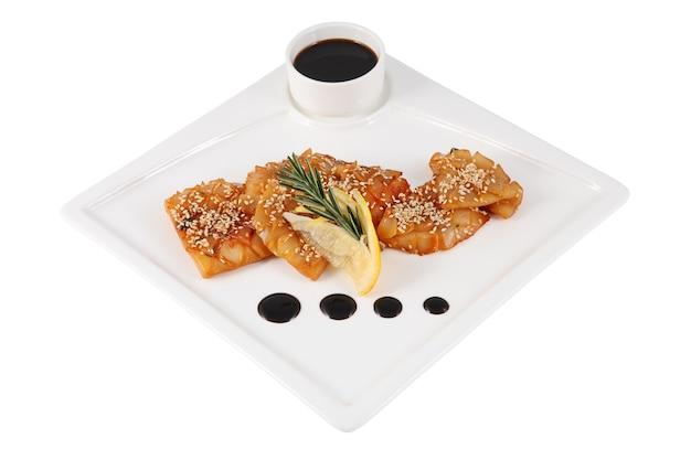 Teriyaki-tintenfisch mit zitrone, sesam und zweigrosmarin auf weißem quadratischem servierteller, lokalisiert auf weißem hintergrund.
