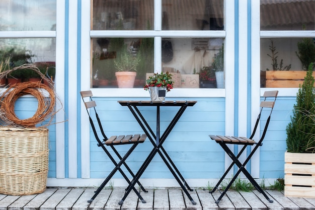 Terrasse mit weidenkörben und grünen pflanzen in töpfen auf der veranda nach hause. holztisch und stühle auf der veranda des hauses. wohnkultur im freien