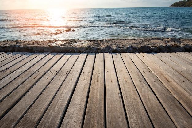 Terrassenblick meer mit leerer hölzerner tischplatte auf der strandlandschaftsnatur mit sonnenuntergang oder sonnenaufgang - holzbrettbalkonblickseelandschaft idyllische küste