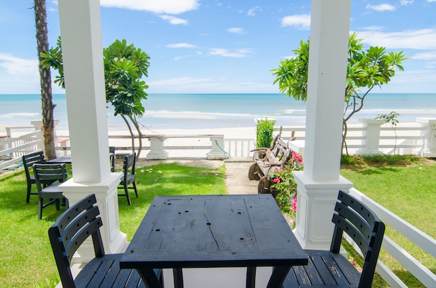 Terrassenmeerblick mit holzstühlen und tisch im freien