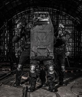 Terrorismusbekämpfung der polizei, taktische gruppe der anti-drogen-kräfte, swat-team versteckt sich hinter einem ballistischen schild, zielt mit waffen und versucht, schüsse während der geiselrettung zu reflektieren, situation aus nächster nähe
