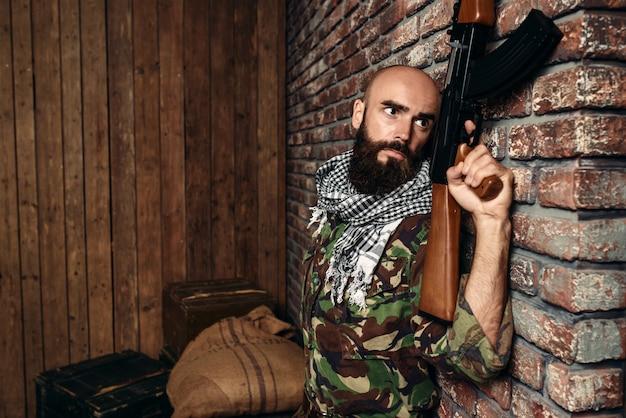 Terrorist mit gewehr versteckt hinter einer mauer