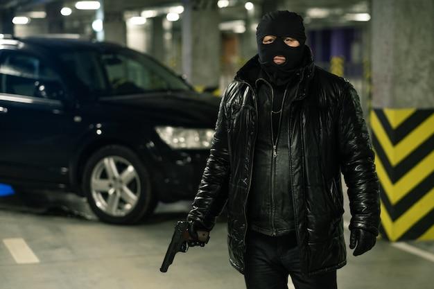Terrorist oder gangster in schwarzer jacke, handschuhen und sturmhaube, die pistole mit auto hält, das auf hintergrund wartet