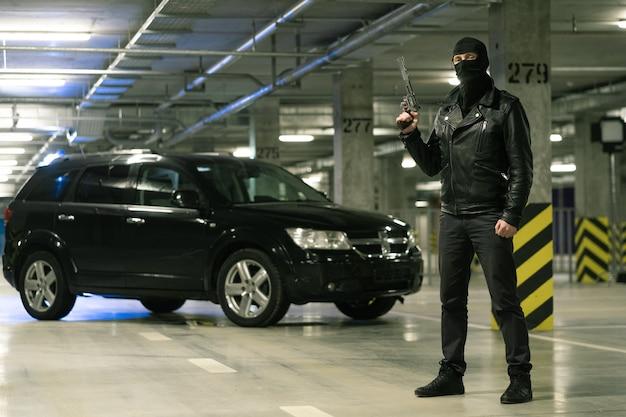Terrorist oder gangster in schwarzer jacke und sturmhaube auf kopf, der pistole hält, die bereit ist, mit auto auf hintergrund zu schießen