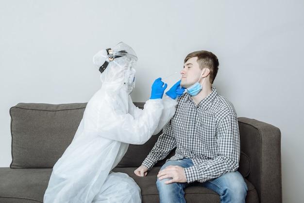 Test auf covid-19. ein arzt in einem psa-schutzanzug, handschuhen und einer maske nimmt einem patienten einen tupfer mit einem wattestäbchen aus nase und mund für das coronavirus.