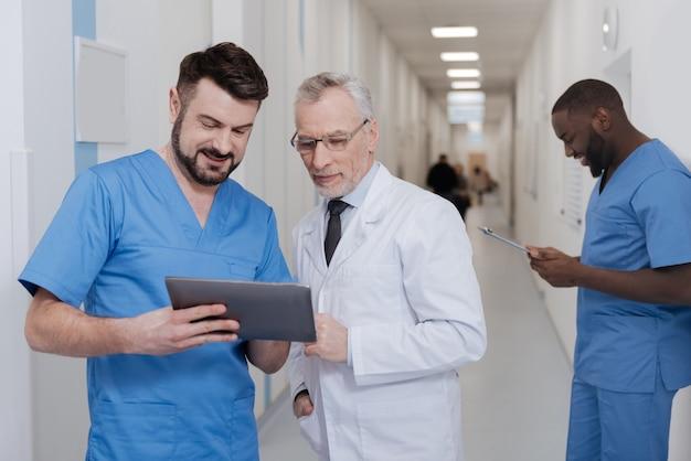 Test-gadget nützlich für die arbeit. interessierte positiv lächelnde mediziner, die im krankenhaus stehen und tablette verwenden, während anderer kollege ordner im hintergrund hält