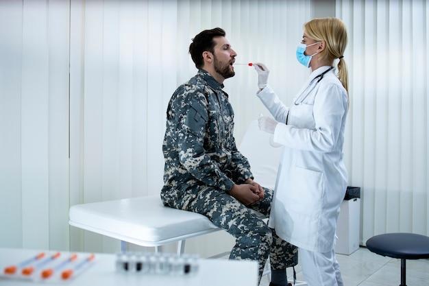 Testen des militärs auf koronavirus soldat in uniform, der einen pcr-test in der arztpraxis während der covid19-virus-epidemie durchführt