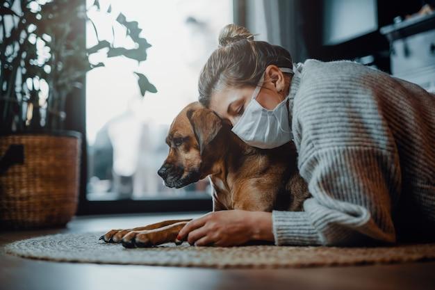 Testen sie uploadfrau, die eine schützende gesichtsmaske trägt, kuschelt, spielt mit ihrem hund zu hause wegen der coronavirus-pandemie covid19