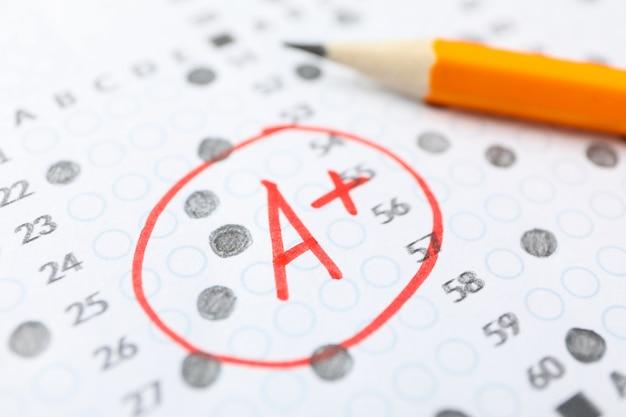 Testergebnisblatt mit antworten, note a + und bleistift, nahaufnahme