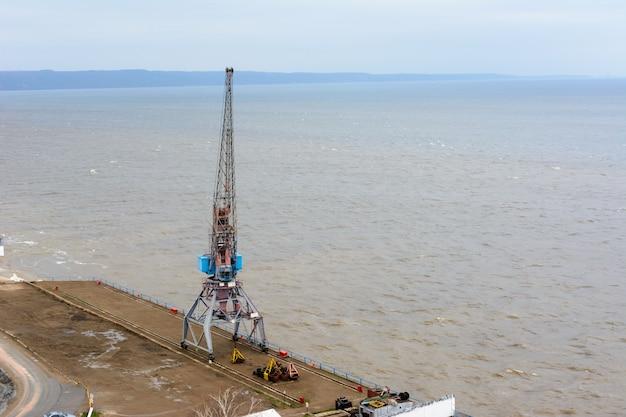 Tetyushi, tatarstan/russland - 2. mai 2019: draufsicht auf den leeren industriepier mit frachthafenkran auf dem dock entlang der geräumigen wolga. die binnenschifffahrt wird nicht beansprucht und nicht genutzt.