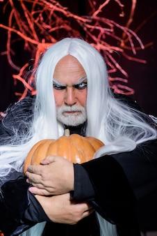 Teufelsmann-design für halloween-party hübscher halloween-mann mit kürbis in der hand glückliches halloween