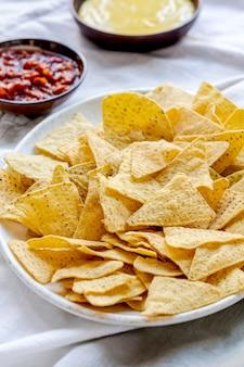 Tex-mex-mais-tortilla-chips mit cheddar-käse-dip und salsa