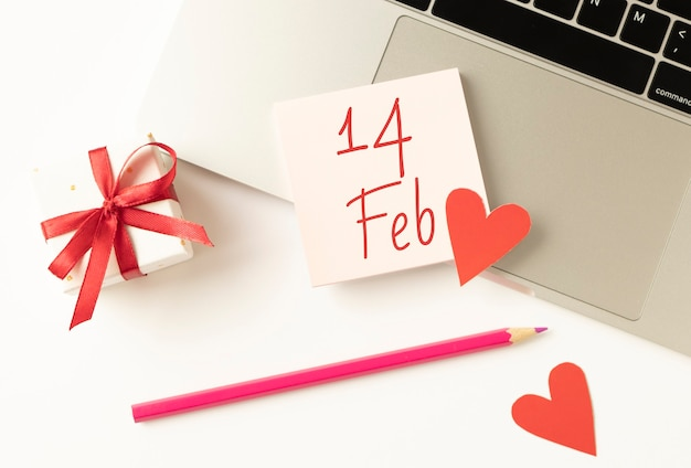 Text 14. februar auf karte mit bleistift, geschenkbox und notizbuch