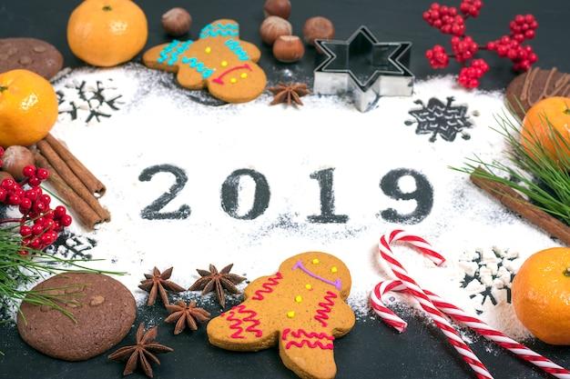 Text 2019 gemacht mit mehl mit dekorationen auf schwarzem hintergrund.
