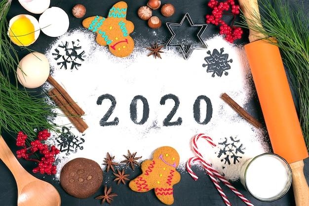 Text 2020 gemacht mit mehl mit dekorationen auf einem schwarzen hintergrund.