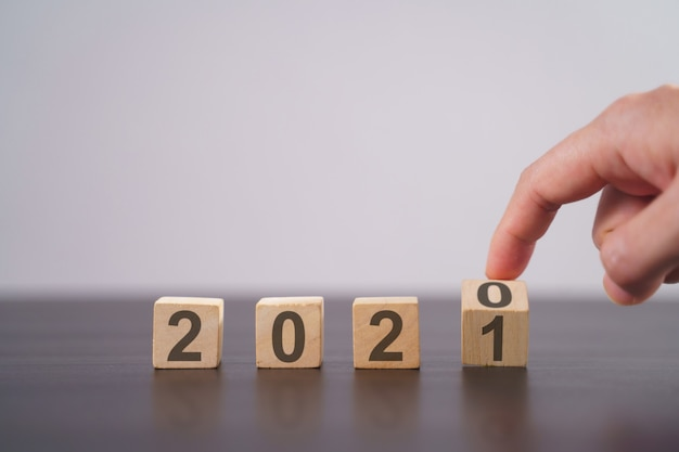 Text 2021 auf holzwürfel isoliert auf grau. neujahrs-countdown-konzept.