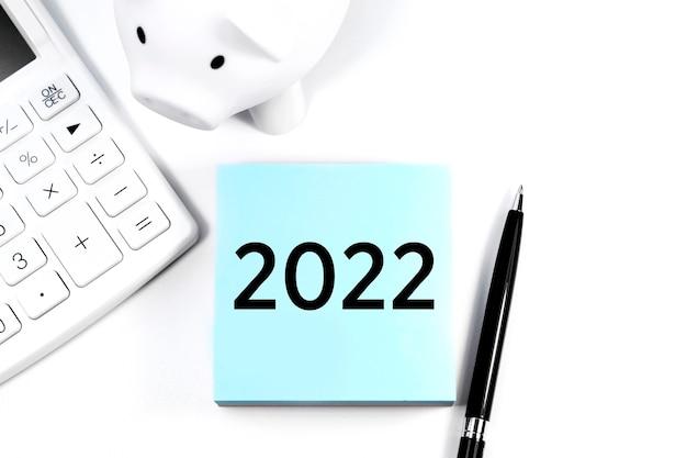 Text 2022 auf aufkleber. rechner, schweinchen und stift. geschäfts- und steuerkonzept auf weißem hintergrund. ansicht von oben.